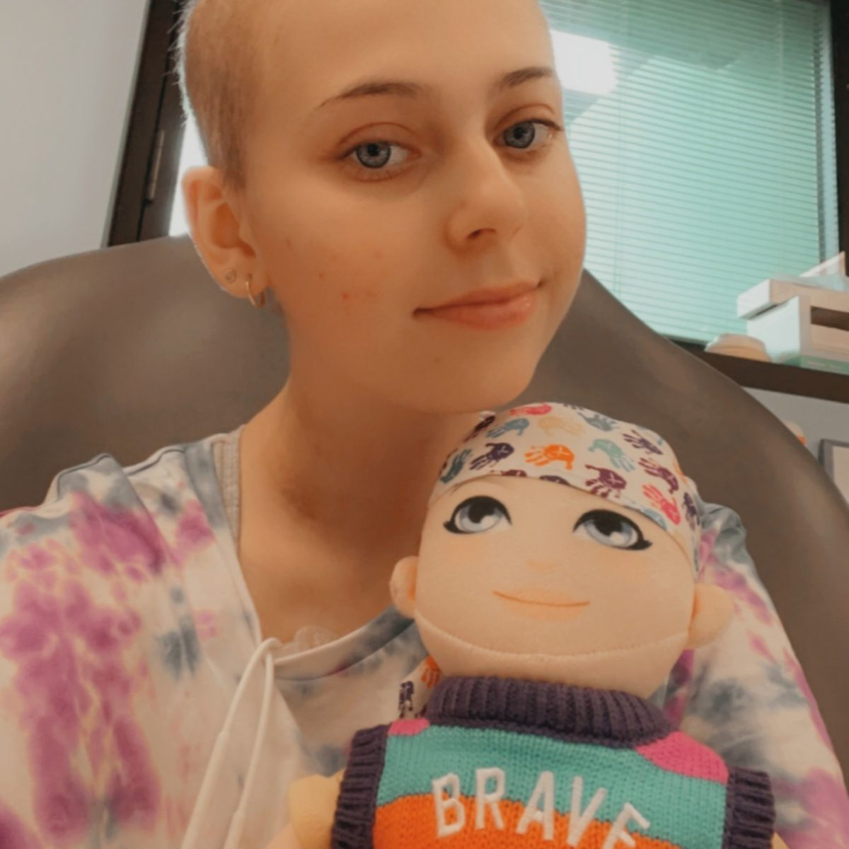 Female teenager, diagnosed with cancer, has lost her hair and is holding a doll wearing a headscarf and a bright striped jumper featuring the word 'Brave'.